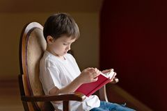 Little boy sitting on old armchair and reading Royalty Free Stock Photo
