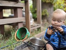 Free Little Boy Sitting On The Ground Looking At And Picking His Muddy Hand Royalty Free Stock Photos - 192820768