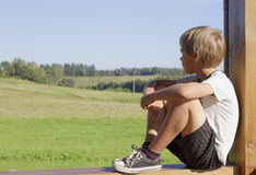 Little boy sitting at outdoors terrace and dreams or thinks about something. Summer day. Green meadows background Royalty Free Stock Photo