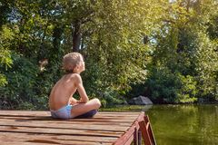 Boy basking in the sun. Little boy sitting on the pier and basking in the sun after swimming royalty free stock photography