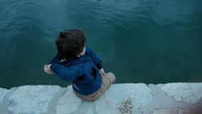 Little boy sitting on pier throws stones into water outdoors. Cute child dressed in blue jacket and beige trousers spends warm autumn day turning to face aqua stock video footage