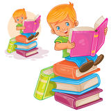 Little boy is sitting on a pile of books and reading another book Royalty Free Stock Images