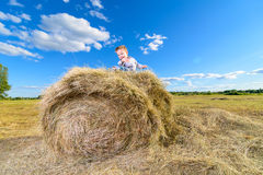 Little boy sitting on a pile of hay  against the blue sky Royalty Free Stock Photo
