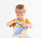 Little boy is sitting and playing with a bucket Stock Image