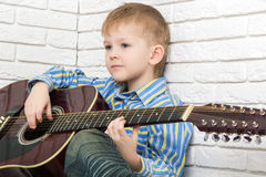Little boy sitting and playing the guitar Stock Photo
