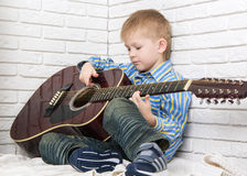 Little boy sitting and playing the guitar Stock Image