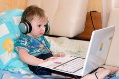Little boy sitting  playing on laptop Stock Photo