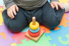 A little boy sitting on a playing mat, collects a multi-colored children`s pyramid. educational toys for children and hand wipes stock image