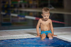 Little boy sitting poolside and dangling legs in water royalty free stock image