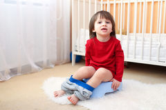Little boy sitting on potty at home. Lovely little boy sitting on potty at home stock photography