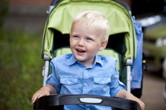 Little boy sitting in pram walking in a summer park. Happy Baby boy sitting in pram walking in a summer park Royalty Free Stock Image