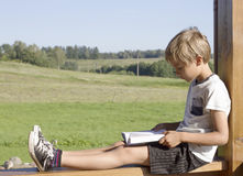 Little boy sitting and reading book at summer terrace. Casual clothes. Nature background. People, education, knowledge Royalty Free Stock Photo