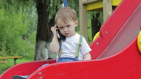 Little boy sitting on a red hill, playground, talking on the phone smartphone stock footage