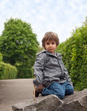 A little boy sitting on a rock. Stock Photo