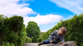 A little boy sitting on a rock. Royalty Free Stock Photos