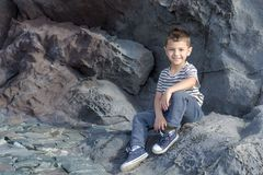 A little boy is sitting on a rock. Little boy sits on a rock against the background of a rock Royalty Free Stock Photos
