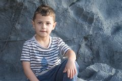 A little boy is sitting on a rock. Little boy sits on a rock against the background of a rock Stock Photo