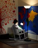 A little boy, sitting in a rocking chair, reads, and a lamp shines above him. Walls - a map of the world and an orange fun tree royalty free stock images