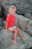 Little boy sitting on the rocks Stock Photo