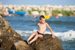 Little boy sitting on rocks at sea Royalty Free Stock Photo