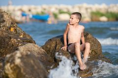 Little boy sitting on rocks at sea Stock Photo