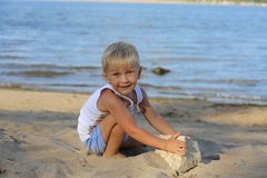 Little boy sitting on the sand on the beach near the river Royalty Free Stock Photo