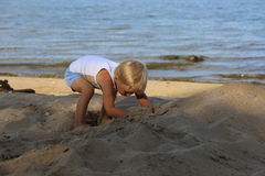 Little boy sitting on the sand on the beach near the river Royalty Free Stock Photos