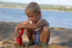 Little boy sitting on the sand on the beach near the river Royalty Free Stock Image