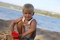 Little boy sitting on the sand on the beach near the river Stock Photo