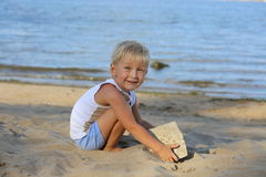 Little boy sitting on the sand on the beach near the river Royalty Free Stock Images