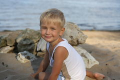 Little boy sitting on the sand on the beach Royalty Free Stock Image