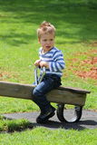 Little boy sitting on the seesaw with green lawn in background Stock Photography