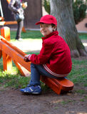 Little boy sitting on seesaw Stock Images