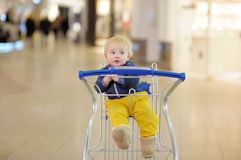 Little boy sitting in the shopping cart Royalty Free Stock Photos