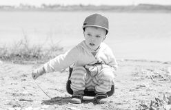 Little boy is sitting on the shore of the lake Stock Images