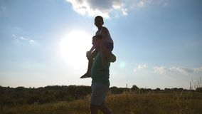 Little boy sitting on shoulders of his daddy while walking at beautiful landscape. Father and son playing on the field stock video