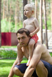 Little boy sitting on the shoulders of a young father Royalty Free Stock Photography
