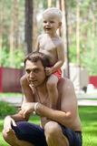 Little boy sitting on the shoulders of a young father Stock Photography