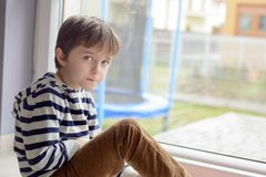 Little boy sitting sitting on the floor in front of a window Stock Photography