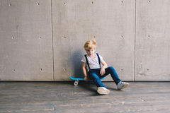 Little boy sitting on a skateboard Royalty Free Stock Photos