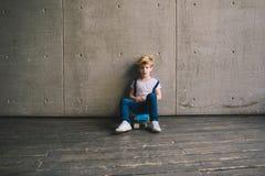 Little boy sitting on a skateboard Stock Photos