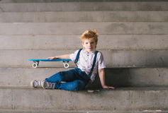 Little boy sitting with a skateboard on the stairs. Copy space Royalty Free Stock Photos