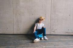 Little boy sitting on a skateboard Stock Image