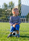 Little boy sitting on a soccer ball Stock Images