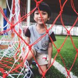 Little boy sitting in Soccer goal net focus on the net Stock Images