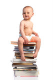 Little boy sitting on a stack of books Royalty Free Stock Photo