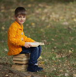 Little boy sitting on stack of books Royalty Free Stock Photo