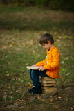 Little boy sitting on stack of books Stock Photo