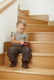 Little boy sitting on stairs Royalty Free Stock Image