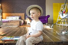 The little boy is sitting on the stairs with a flashlight in hand. Royalty Free Stock Image